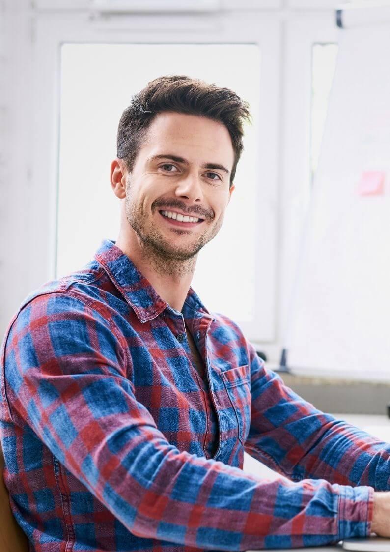 Chef d'entreprise heureux avec sa chemise à carreaux